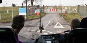 Image showing the front window of a bus and the driver. The bus is parked in front of a Qinetiq base.