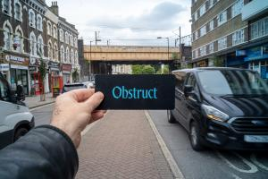 A white skinned hand holds a small black card up with the words 'Obstruct' in turquoise letters typed on. The person is standing on a busy street in a city with tall buildings with cars going past.