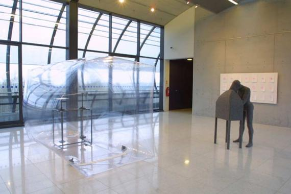 A large gallery space, showing a large transparent cube and a sculpture of a figure looking in to a box.