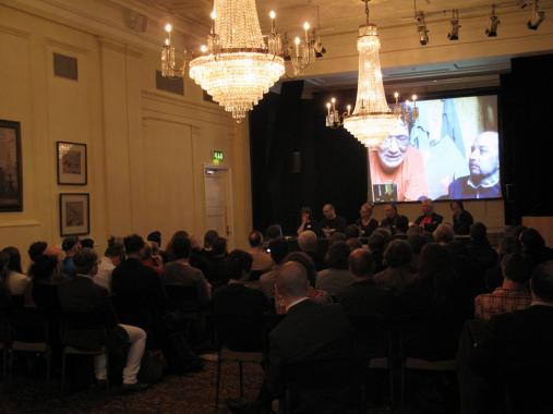 The Arctic Perspective Initiative panel sit at the front of a large grand room with chandeliers in Canada House. The audience are asking questions