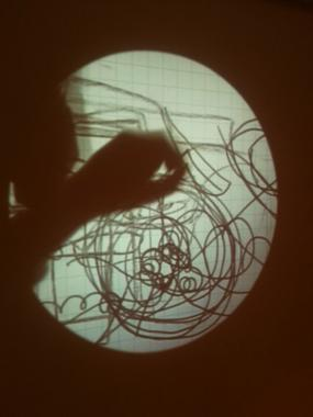 Circular projection of an interactive drawing, with a hand casting a silhouette.