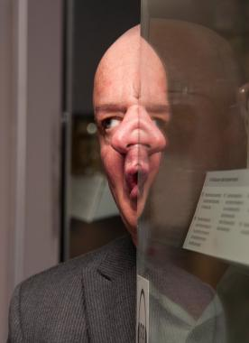 Aaron Williamson distorts his face using a glass cabinet at The Huntarian Museum.