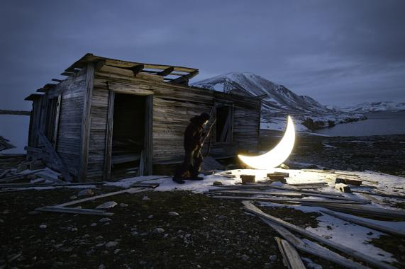 An illuminated crescent moon standing in front of a cabin located in a snowy mountainous region.