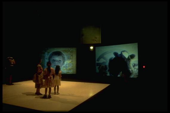 Young girls stand on a platform looking upon two video installations.