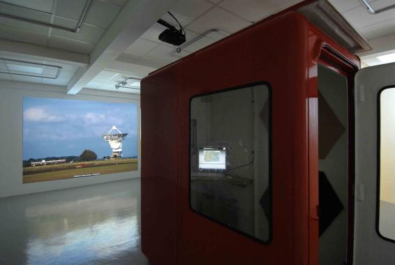 A red information kiosk placed in a gallery space, presenting details on sites of interest around the UK. Behind the kiosk, a large photograph of a dish radio telescope.