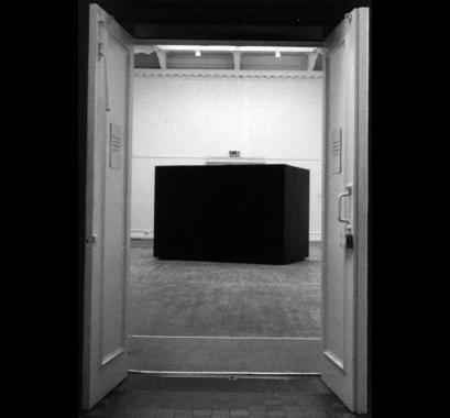 A large sound/light proof black box in a gallery space. Biswas inhabited this box for ten days.