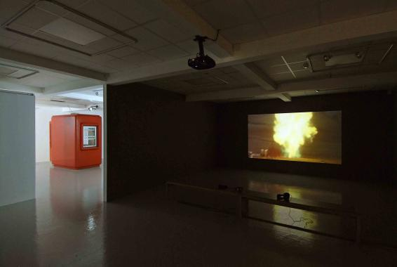 "A projection of the film ""Voodoo Science Park"" where large disasters are recreated. In the film, a large fire blazes."