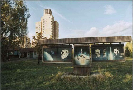 Space flight photographs installed on a wooden structure. A large block of flats sits in the background.