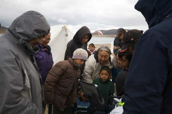 Igloolik citizens crowd around a computer, engaging with Marko Peljhan's mobile media project.