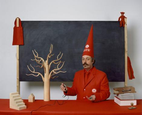 Benedict Phillips sits in front of a blackboard wearing a dunce hat. He is surrounded by wooden objects, and is holding a timer.