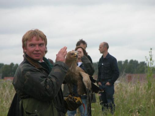 Man holds eagle used to document the moving public on the ground