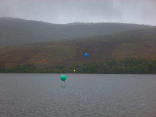 Large green, blue and yellow balloons float above Loch Ruthven
