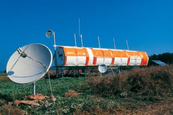 Large hexagonal cylinder shaped laboratory in field, satellite dish in foreground.
