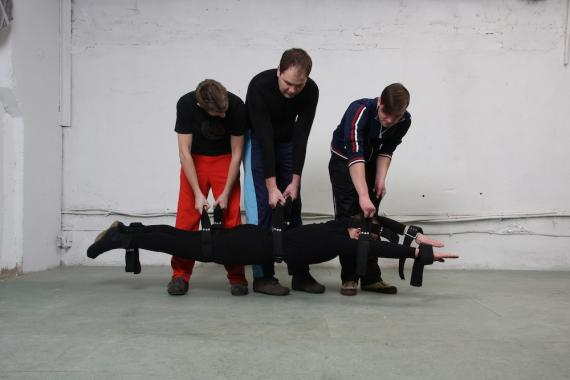"Three men hold straps connected to a man, allowing him to ""float"" above the floor."