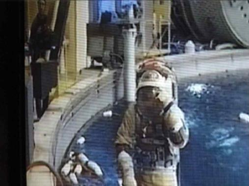 An astronaut sits in a pool.