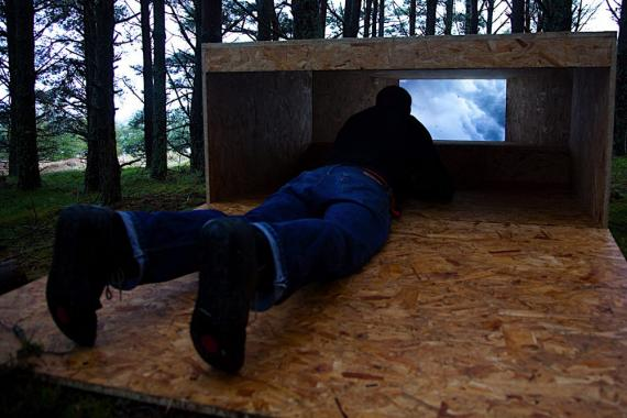 A man lies face down within a wooden structure in woodland, gazing through a window which shows a blue sky with clouds.