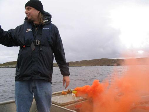 A member of Critcal Arts Ensemble stands beside a canister emitting orange smoke, on board a boat.