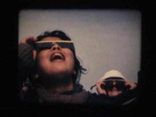 A woman wearing darkened sunglasses to watch the solar eclipse.