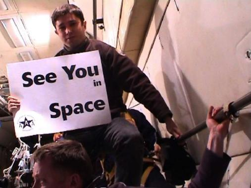 "Photograph of Ewen Chardronnet floating with a sign which states ""See You In Space""."