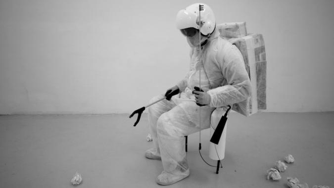 An astronaut sits in a gallery space with a handheld rubbish picker, surrounded by balls of paper.